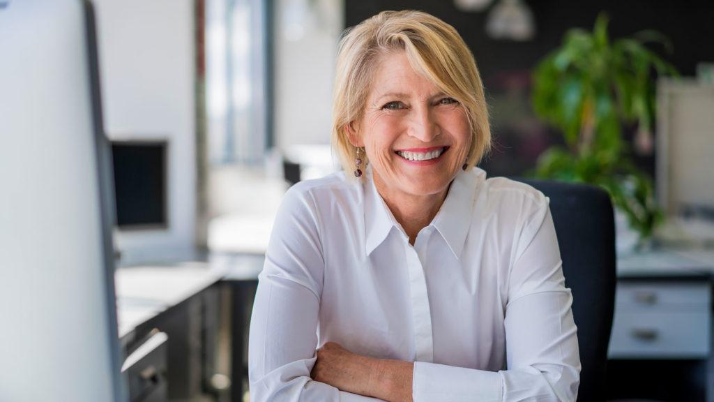 happy-mature-businesswoman-sitting-at-desk