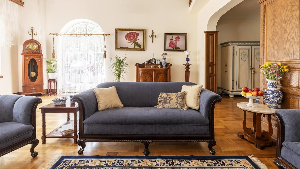 Cobalt Blue Sofa And Other Antique Furniture On A Wooden Floor In A Spacious Living Room 2